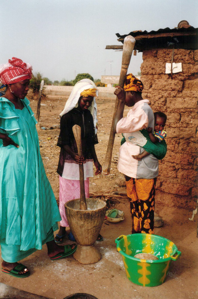 Women pounding maize in wooden mortar